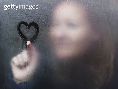 Woman drawing a heart in the condensation on window. - gettyimageskorea