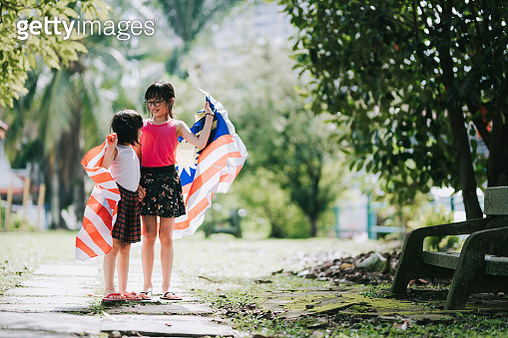 2 asian chinese young girl playing and spending bonding time in public park wrapping with malaysia national flag - gettyimageskorea