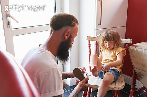 Dad putting toddler daughter's sandals on - gettyimageskorea