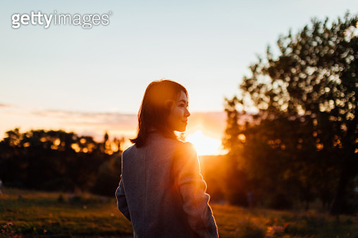 Young Woman Watching Sunset While Enjoying Nature - gettyimageskorea