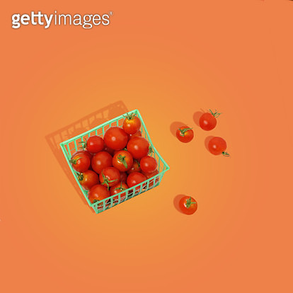 Red cherry tomatoes in a plastic basket on an orange background. - gettyimageskorea