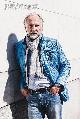 Portrait of fashionable mature man leaning against a wall - gettyimageskorea