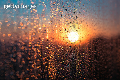 Wet Window with Condensation Water Against Sunrise or Sunset Glow in Cold Winter Day, Warm Indoor - gettyimageskorea