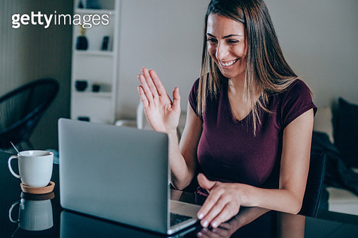 Beautiful young woman having video call at home. Shot of a young woman using a laptop for video conference. - gettyimageskorea