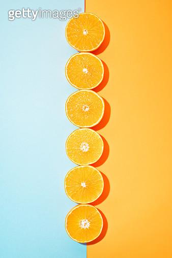 Halved Oranges on Blue and Orange Background - gettyimageskorea