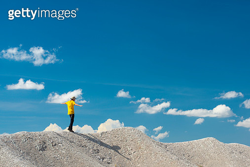 Man balancing on top of a white hill. Dressed in yellow with a hat and clear blue sky on the background. - gettyimageskorea