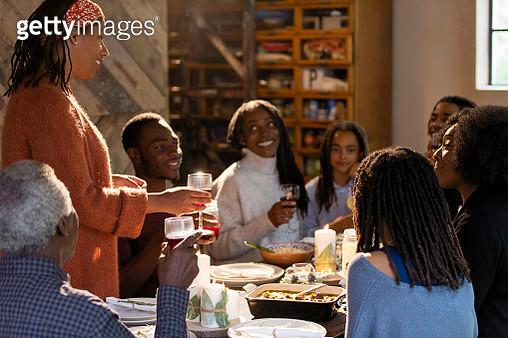 Woman toasting multi-generation family at Christmas dinner table - gettyimageskorea