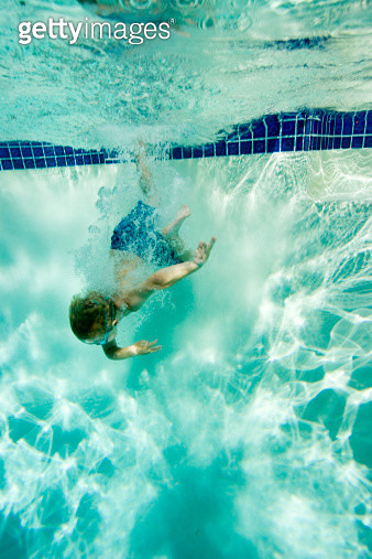 An underwater view of a young boy diving into a pool. - gettyimageskorea