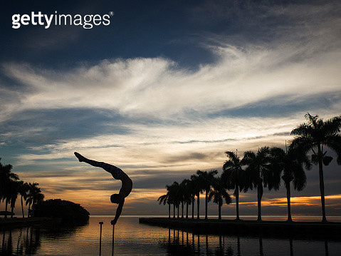 Mature man balancing on pole in water, dusk, South Pointe Park, South Beach, Miami, Florida, USA - gettyimageskorea
