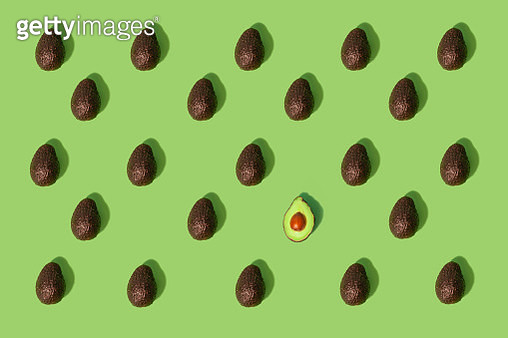 Concept stand out from the crowd  Large group of whole avocados placed in a repeating pattern where one split in half stands out from the crowd - gettyimageskorea