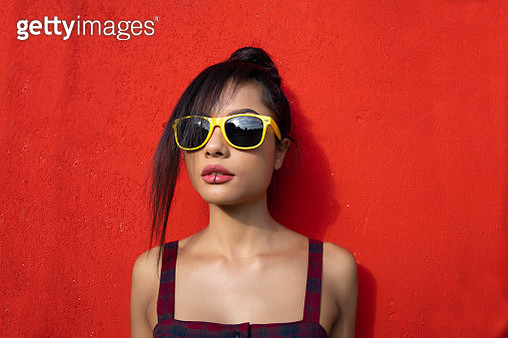 Beautiful woman standing in front of red background - gettyimageskorea