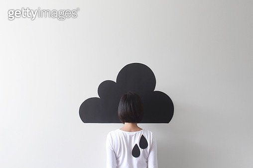Rear view of a woman standing against conceptual rain cloud - gettyimageskorea