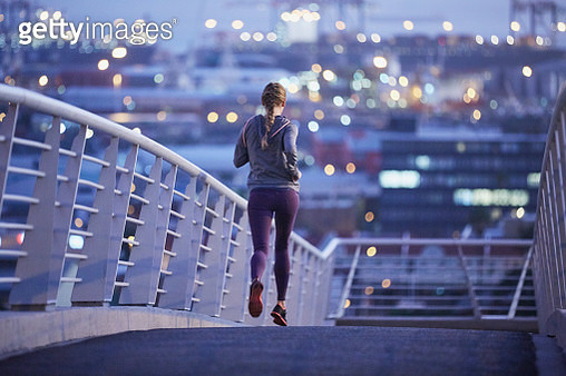 Female runner running on urban footbridge at dawn - gettyimageskorea