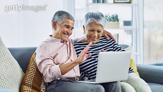 Shot of a senior couple waving while using a laptop together on the sofa at home - gettyimageskorea