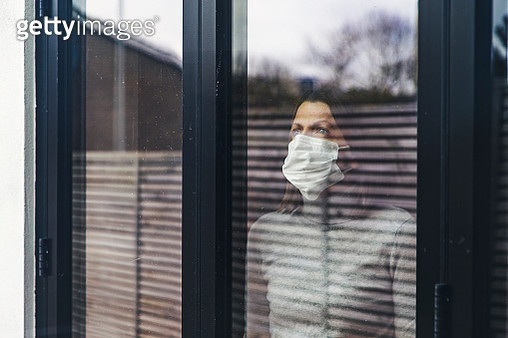 Woman with mask looking out of window - gettyimageskorea