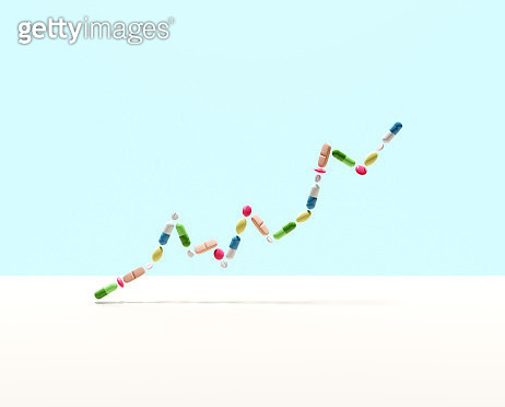 Medical capsules and pills forming a line graph - gettyimageskorea