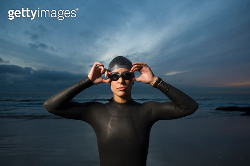 Hispanic woman in wetsuit on beach - gettyimageskorea