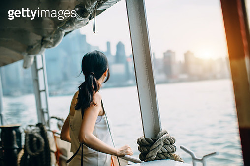 Young woman looking over the spectacular city skyline of Hong Kong at dusk while riding on Star Ferry - gettyimageskorea
