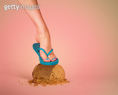 A woman's foot in teal polka dot flip flops with painted toenails smashes a giant peanut butter cookie on a peach colored background. Dieting concept. Room for copy. - gettyimageskorea