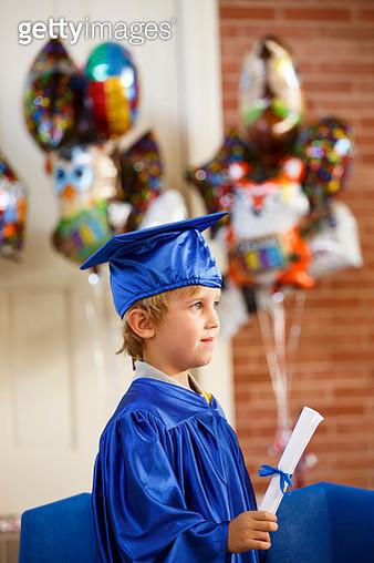Caucasian boy wearing graduation robe holding diploma - gettyimageskorea