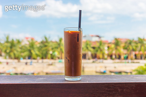 Vietnamese iced coffee on table during a sunny day . Hoi An in background . - gettyimageskorea