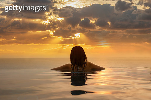 Woman in infinity pool at sunset. - gettyimageskorea