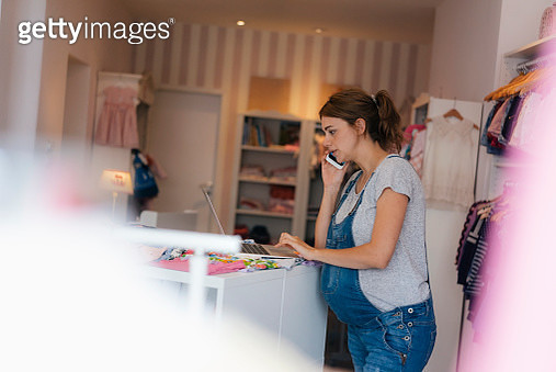 Pregnant woman using cell phone and laptop in a boutique for baby clothing - gettyimageskorea