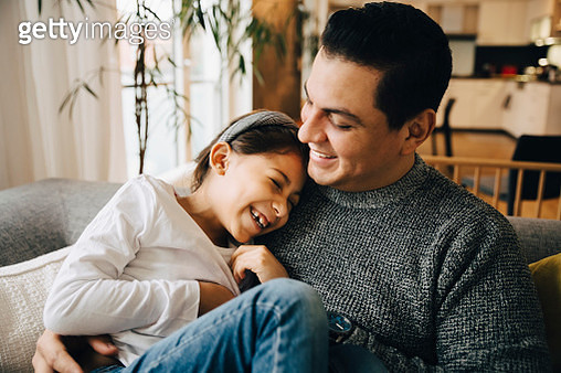 Smiling father and daughter spending leisure time while sitting on sofa at home - gettyimageskorea
