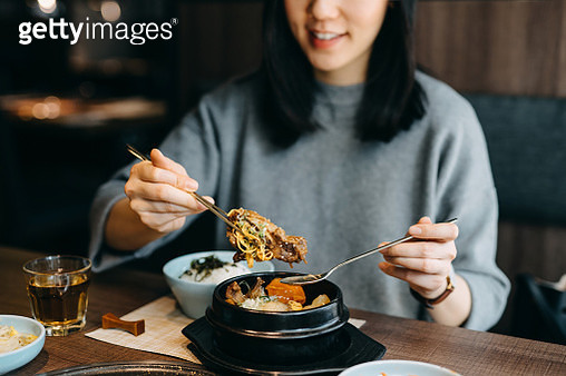Smiling young Asian woman enjoying Korean meal in a Korean restaurant - gettyimageskorea