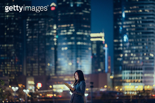 Pretty businesswoman using digital tablet in city - gettyimageskorea