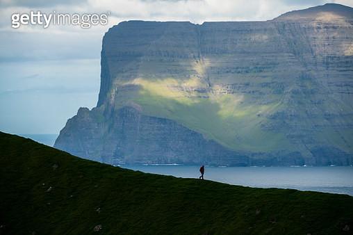 Hiker looks towards Vidoy island, Faroe Islands - gettyimageskorea