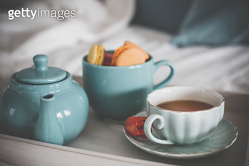 Close up shot of a breakfast tray set up on a bed with a cup of coffee, tea pot and cup full of delicious macaroons as a little breakfast treat. There is also a tulip as a decoration. - gettyimageskorea