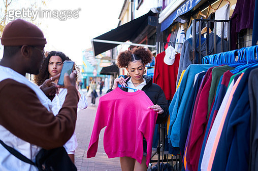 Group of friends trying on vintage clothing and posing for pictures - gettyimageskorea