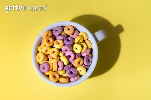 Colorful Corn Rings In Cup On Yellow Background - gettyimageskorea