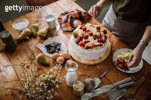 Woman Decorating Cake With Lemon, Lime And Strawberries - gettyimageskorea