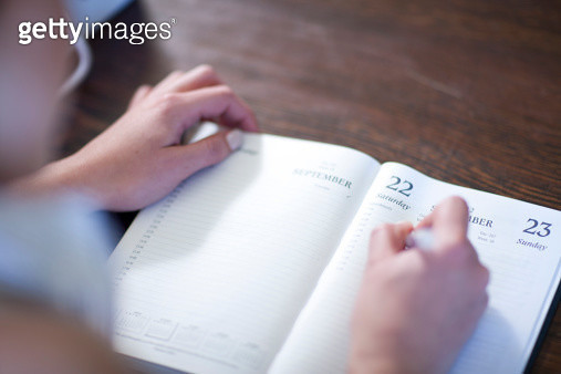 Close up of female writing in diary - gettyimageskorea