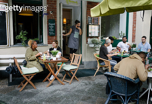 Busy Restaurant Facade With People Sitting And Eating - gettyimageskorea