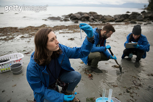 Curious eco-friendly female scientist gathering water specimens on beach - gettyimageskorea