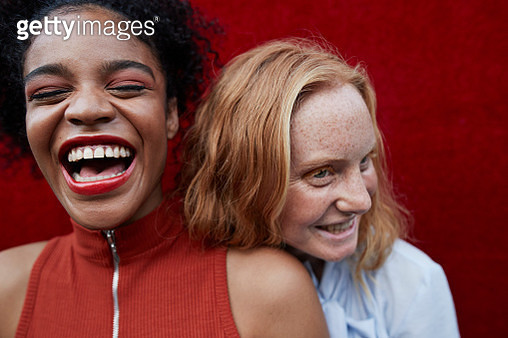Close-up of young women laughing while standing against red wall - gettyimageskorea