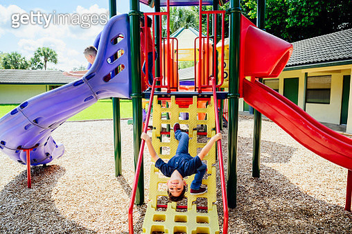 Smiling elementary aged Hispanic schoolboy hanging upside down on outdoor playground equipment during recess break. - gettyimageskorea