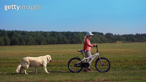 Side View Of Girl With Bicycle Walking On Grassy Field - gettyimageskorea