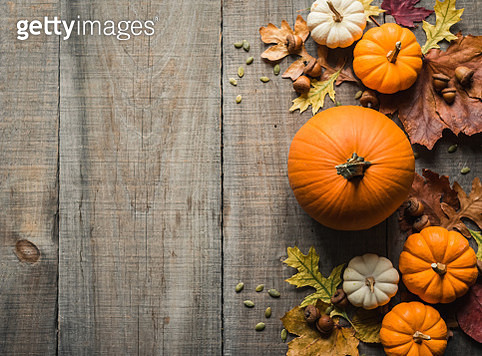 Overhead view of pumpkins and other fall decor on rustic wooden table. - gettyimageskorea