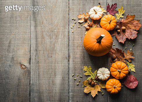 Overhead view of pumpkins, leaves and acorns on a rustic wooden table. - gettyimageskorea