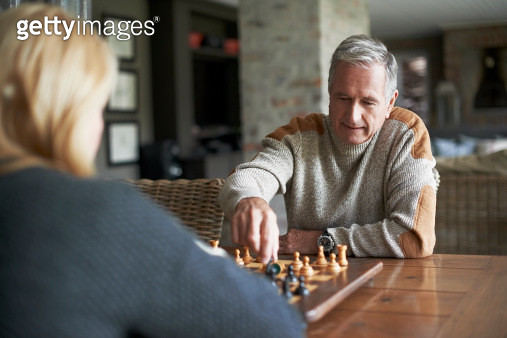 Happy senior woman playing chess with man at table in house - gettyimageskorea