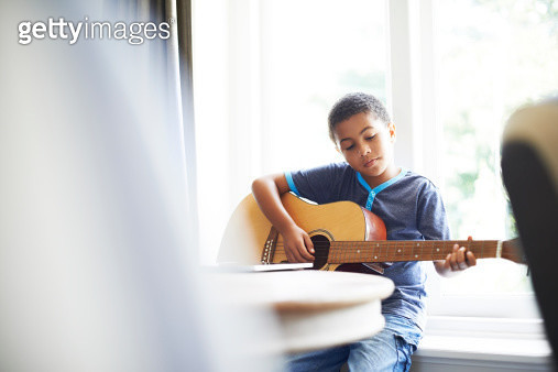 Little boy playing guitar while sitting on window sill at home - gettyimageskorea