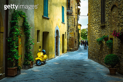 Small narrow street with traditional yellow houses in Tuscan village of Pienza, Italy - gettyimageskorea