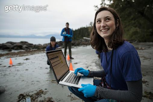 Portrait smiling, confident eco-friendly female scientist with laptop on beach - gettyimageskorea