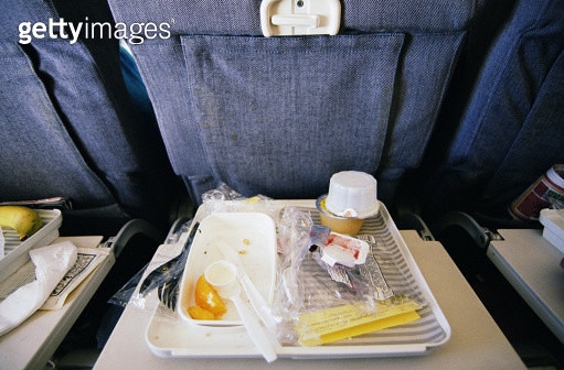 Airline food wrappers and utensils on tray, elevated view - gettyimageskorea