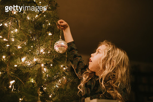 Little Girl Decorating Christmas Tree with Ornaments - gettyimageskorea