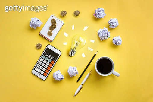 Conceptual financial or business planning brain storming session and light bulb on yellow table top image. - gettyimageskorea